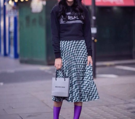 Girl in a midi skirt, black sweatshirt and purple ankle boots